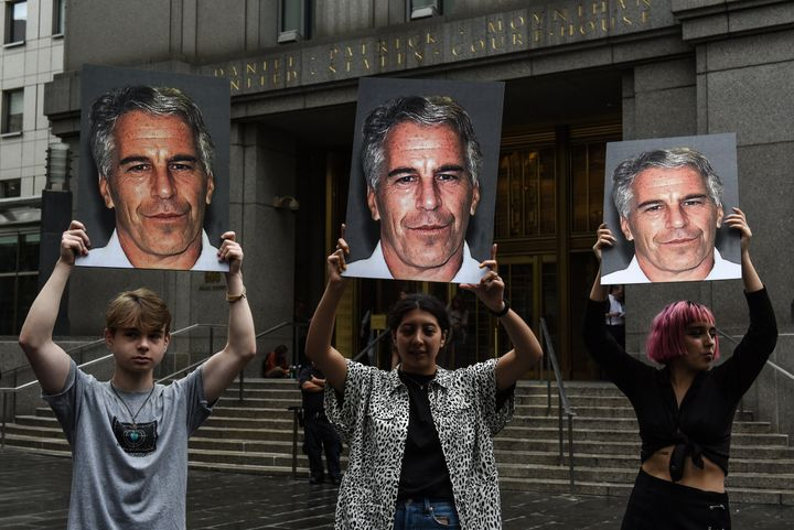 """A protest group called """"Hot Mess"""" hold up signs of Jeffrey Epstein in front of the Federal courthouse on July 8, 2019 in New York City."""