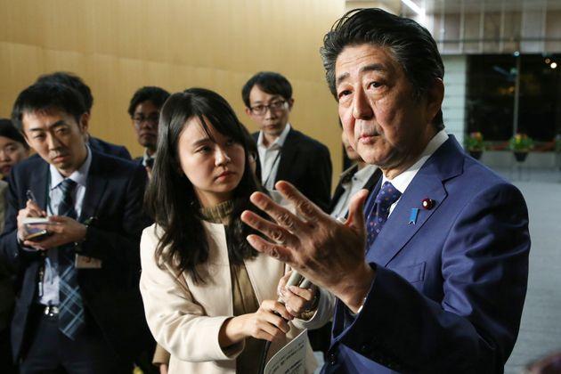 記者団の質問に答える安倍晋三首相(右)=11月15日夜、首相官邸