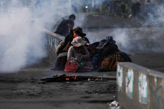 Apoiadores do ex-presidente Evo Morales sentam-se no chão durante confrontos com as forças...