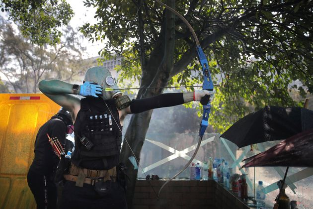 A protestor prepares to fire a bow and arrow during a confrontation with police at the Hong Kong Polytechnic...