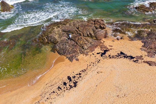 Voluntário tenta remover mancha de óleo da praia de Busca Vida, em Camaçari, na