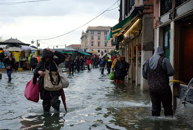 People walk in a flooded street during a period of seasonal high water in Venice, Italy, November 17,...