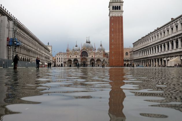Tourists walk in St. Mark's Square after days of severe flooding in Venice, Italy, November 17, 2019....