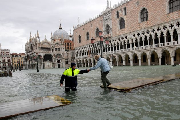 A city worker helps a woman who decided to cross St. Mark's Square on a gangway, in spite of it being...