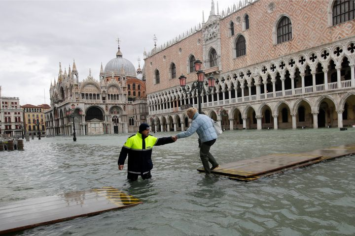 A city worker helps a woman who decided to cross St. Mark's Square on a gangway, in spite of it being closed, in Venice, Ital