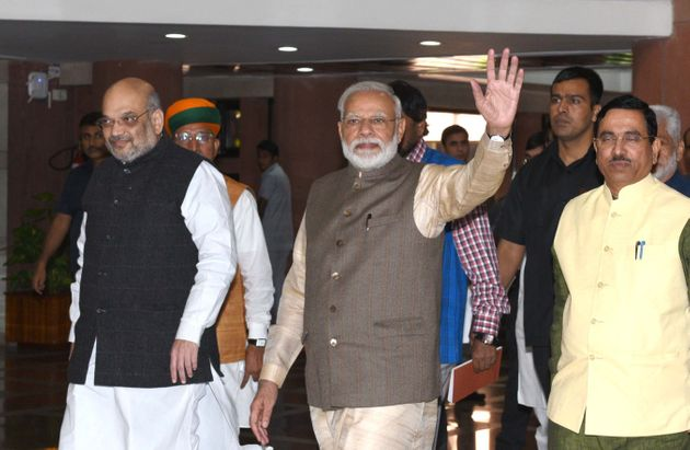 Prime Minister Narendra Modi waves as he, along with Home Minister Amit Shah, Union Parliamentary Affairs...