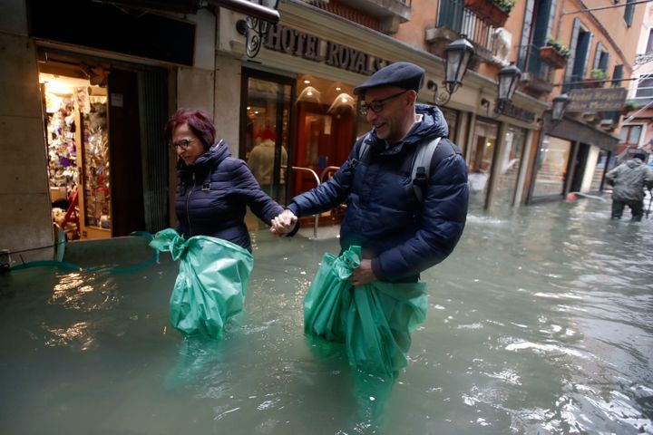 A couple wades their way through water in Venice, Italy, on Nov. 15, 2019.