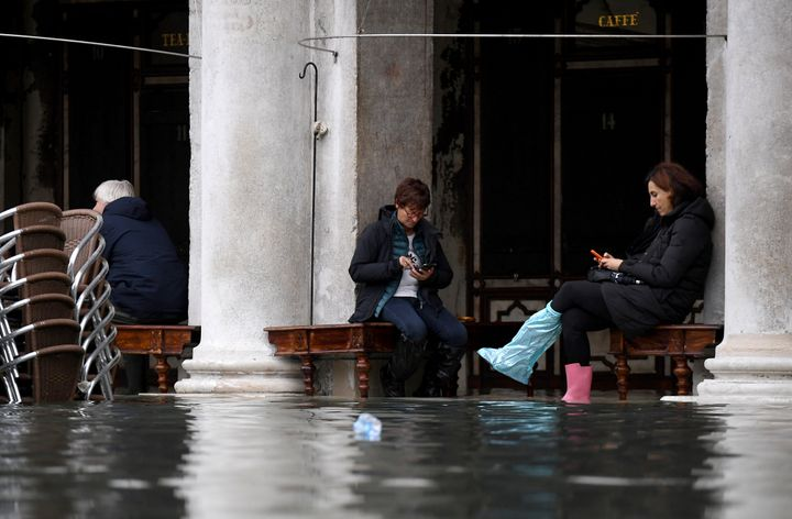 People sit outside a cafe under arcades at St. Mark's Square during high tide in Venice, Italy, on Nov. 17, 2019.