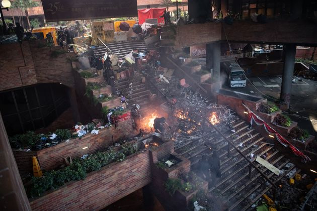 aHONG KONG, CHINA - NOVEMBER 18: Anti-government protesters walk past a fire during clashes with police...