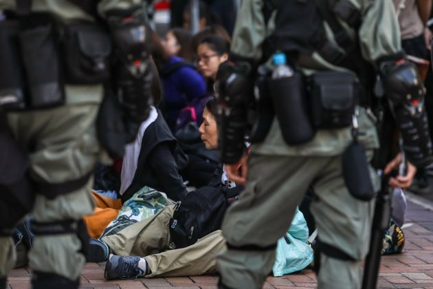People are detained by police near the Hong Kong Polytechnic University in Hung Hom district of Hong...