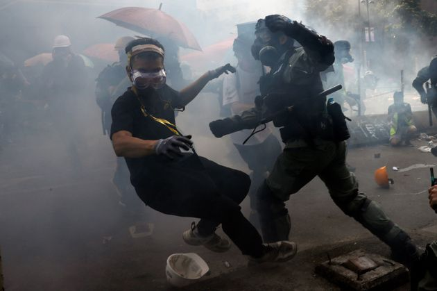 A protester is detained by riot police while attempting to leave the campus of Hong Kong Polytechnic...