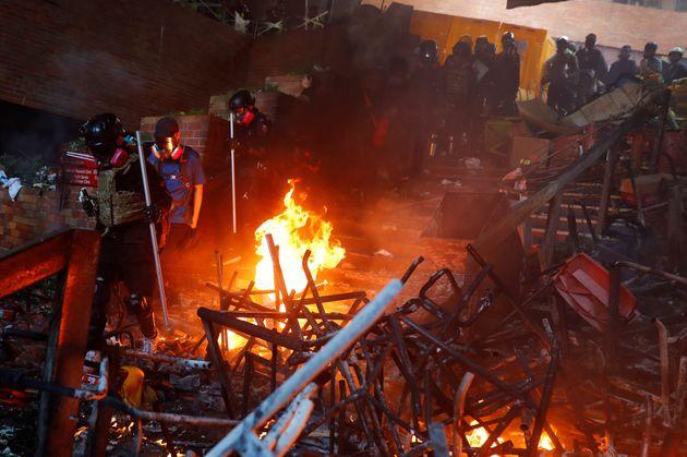 Police storm the burning barricade at the Hong Kong Polytechnic University