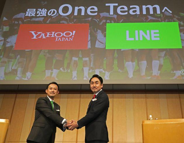 経営統合に関する共同記者会見で握手するZホールディングスの川邊健太郎CEOとLINEの出澤剛CEO=11月18日、東京都港区