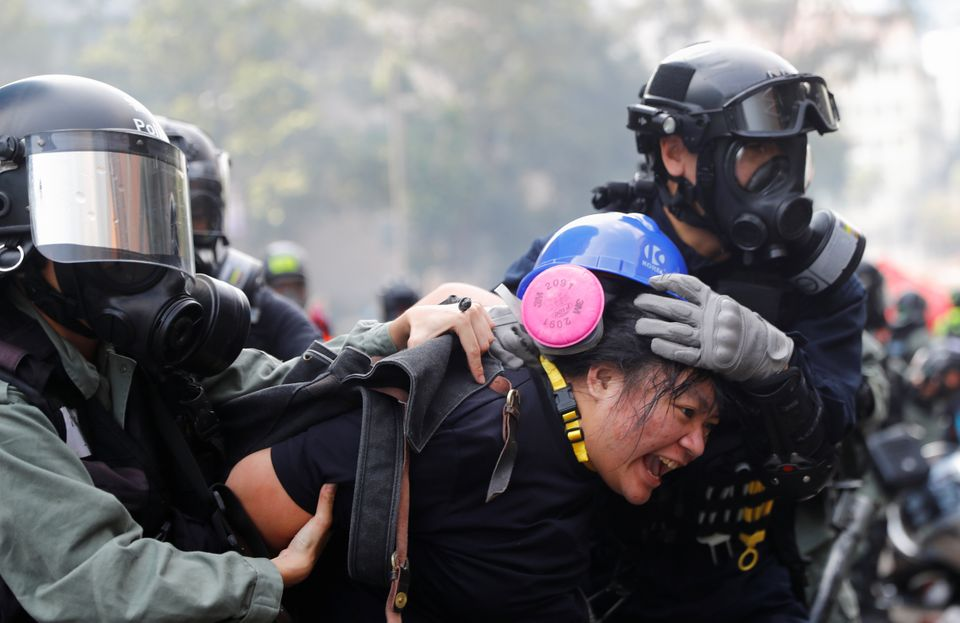 A protester is detained by riot police while attempting to leave