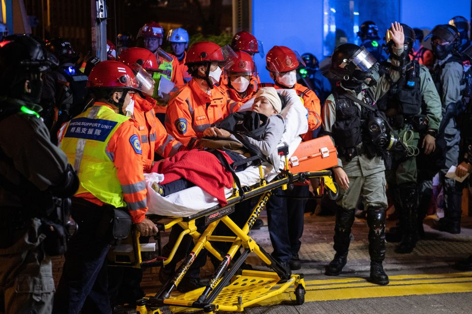 Injured people are taken away after clashes between anti-government protesters and police on