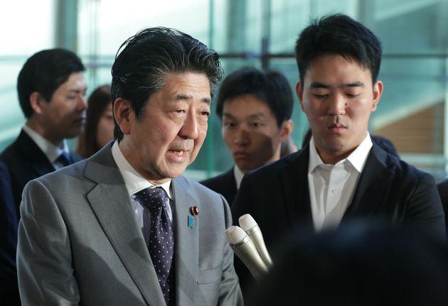 記者団の質問に答える安倍晋三首相(左)