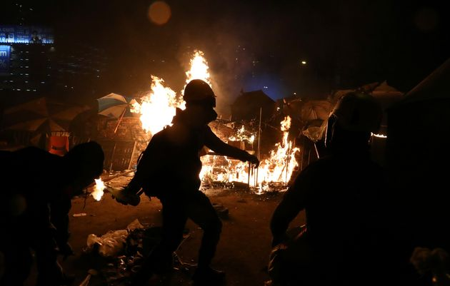 An anti-government protester throws a molotov cocktail during clashes with police, outside Hong Kong...