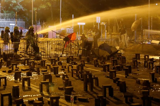 Firefighters work to put out a fire after the clashes between anti-government protesters and police near...