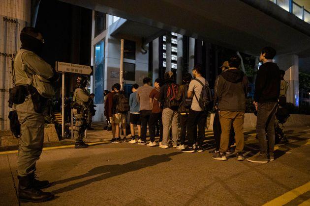 미성년 시위대가 홍콩 폴리테크닉대학교의 경찰 체크포인트를 통과해 투항하고