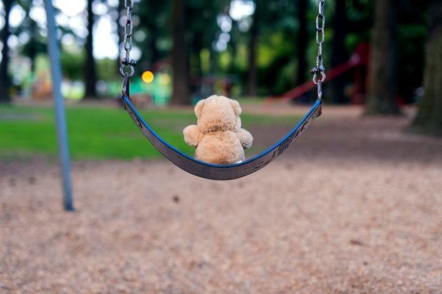 Teddybear sitting alone on a swing set at the