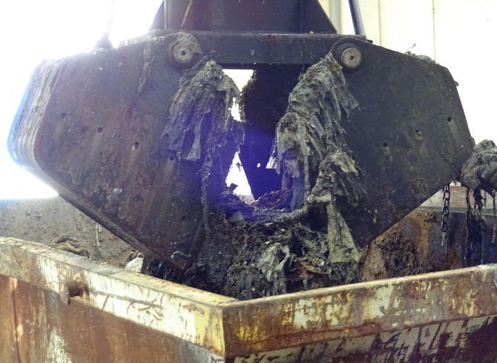 Pala anfibia que recoge los residuos sólidos en la planta depuradora de Arroyo Culebro.