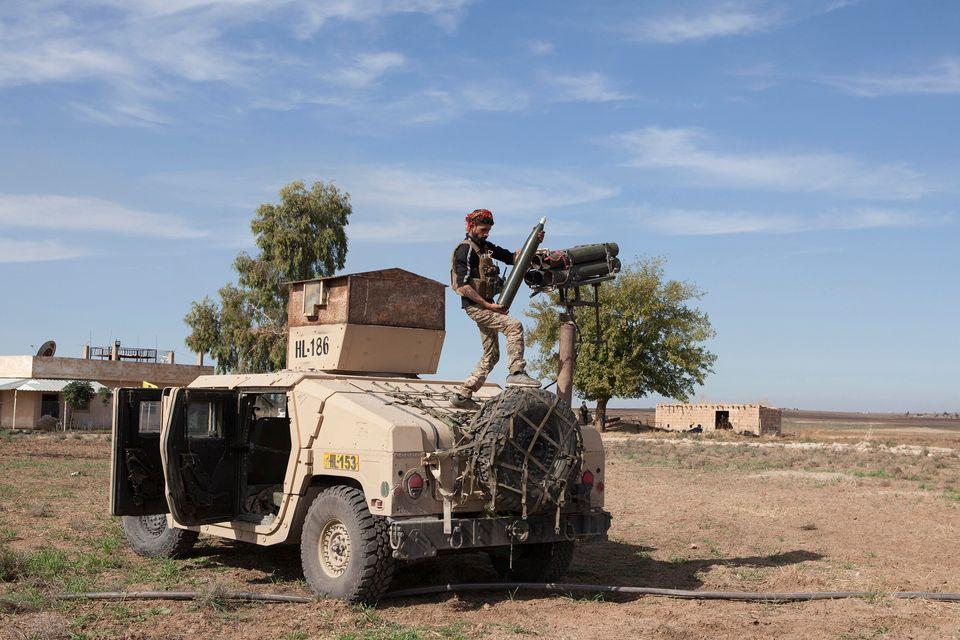 Un guerrigliero curdo carica un lanciarazzi per colpire i villaggi occupati dalle truppe turche e