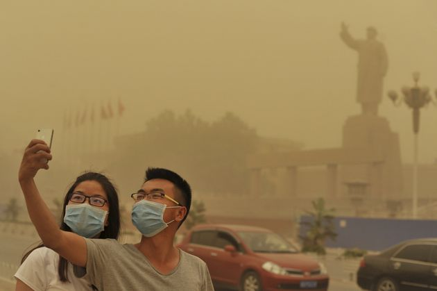 Residents wearing masks pose for a photograph near a statue of late Chinese Chairman Mao Zedong, as a...