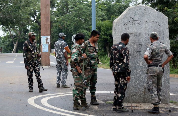 This photo taken on June 26, 2018 shows Indian security forces looking at stone monoliths displaying an allegiance to Pathalgadi -- a popular indigenous tribal movement -- at the entrance to a tribal-dominated region in Khunti district in India's eastern Jharkhand state.
