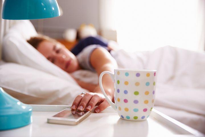 Sleeping Couple Being Woken By Mobile Phone In Bedroom
