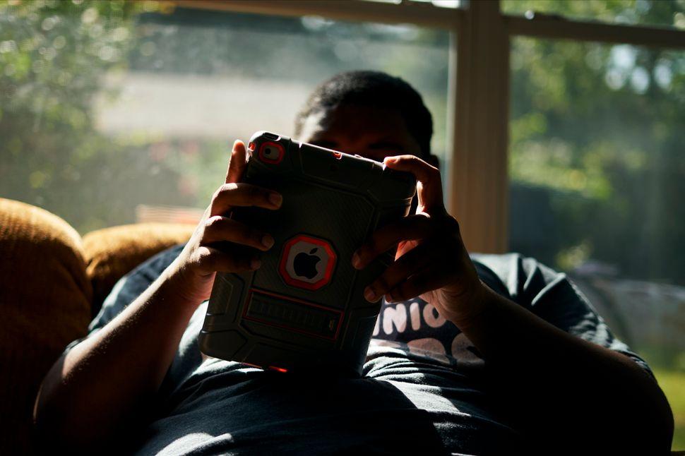 J.H. escucha música en su iPad en la terraza acristalada de su casa en Shreveport, Louisiana, en agosto