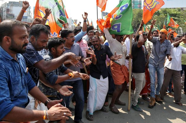 Supporters of BJP shout slogans as they block a highway during a protest against the arrest of their...