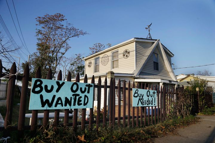 "Signs asking for a ""buy out"" hang in front of a home damaged by Hurricaine Sandy on Staten Island, New York."