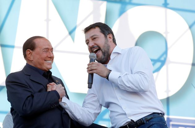 League party leader Matteo Salvini welcomes former Italian Prime Minister Silvio Berlusconi on stage...