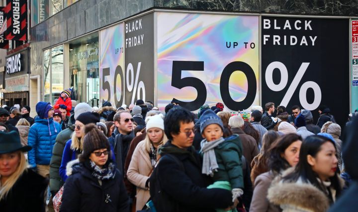 Crowds walk past a large store sign displaying a Black Friday discount in midtown Manhattan, Nov. 23, 2018, in New York City.