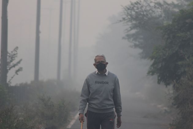 NEW DELHI, INDIA - 2019/11/15: A man wearing a protective mask jogs on a foggy morning in Noida on the...