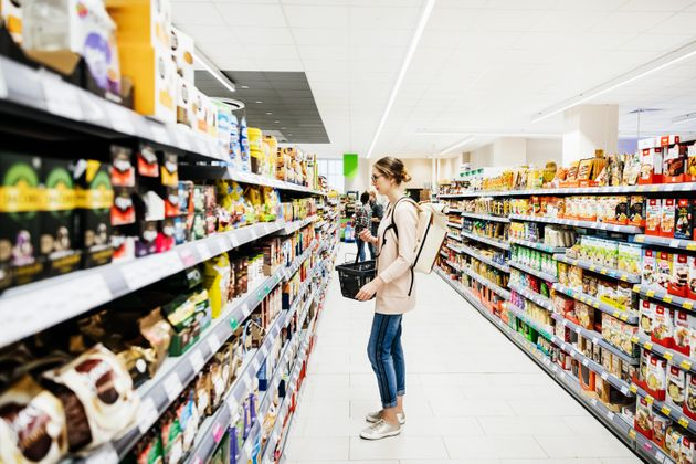A colorful supermarket aisle with people shopping for