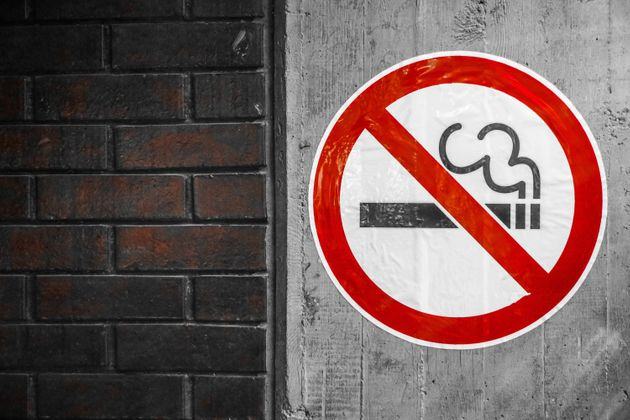 Smoking is not allowed sign on a concrete wall, brick wall on