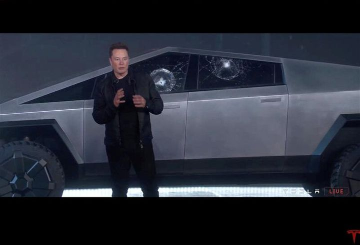 Tesla chief executive Elon Musk stands in front the company's first electric pickup truck, the Cybertruck, in Los Angeles on Thursday after windows were smashed with a metal ball.