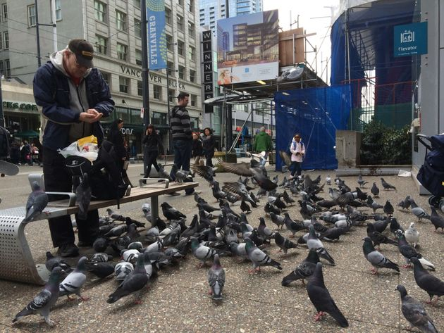 A man feeding pigeons in downtown