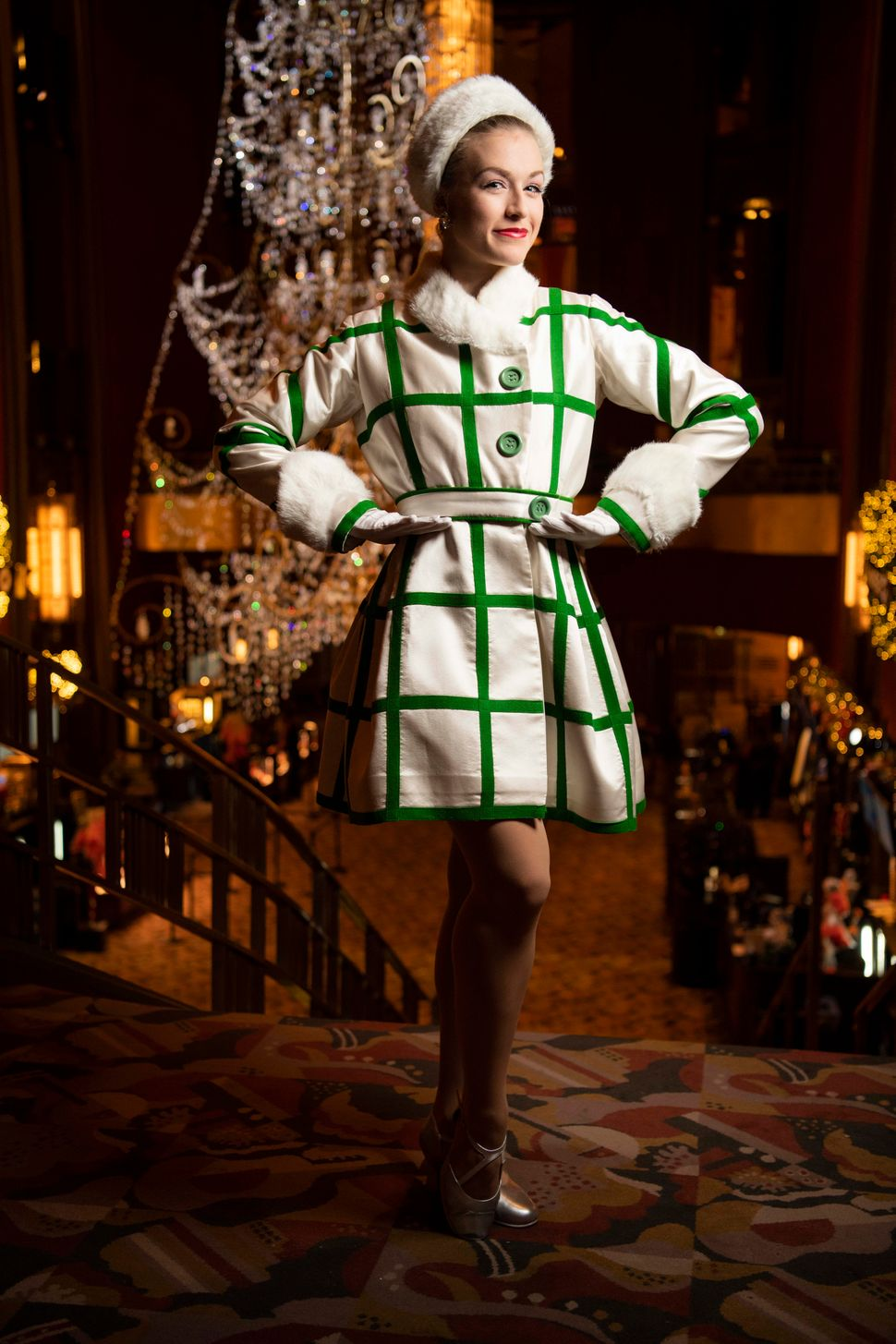 "Maddie Rodrigue in the ""New York at Christmas"" look. Rockettes wear either green or red coats with the same sparkly red dress beneath it, and follow choreography based on their coat color."