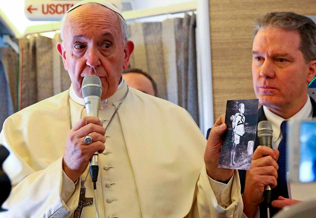 専用機内で「焼き場に立つ少年」のカードを記者団に示すフランシスコ教皇