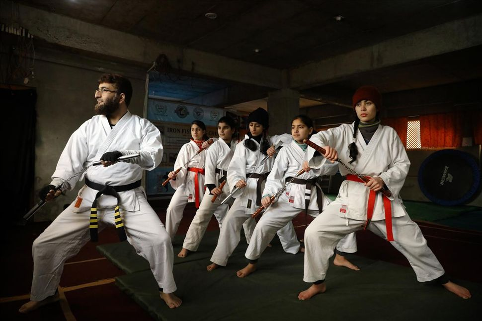 Peerzada Adil Iqbal Shah leading girl studentsduring a training session at his martial arts academy in Soura, Srinagar.