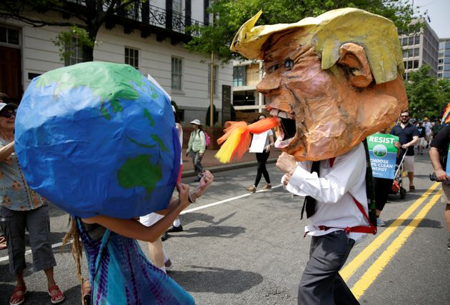 Protesters dressed as the Earth and President Donald Trump pretend to fight during the People's Climate...