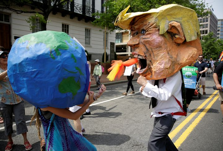 Protesters dressed as the Earth and President Donald Trump pretend to fight during the People's Climate March near the White