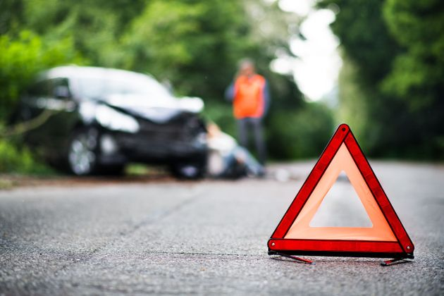 A close up of a red emergency triangle on the road in front of a damaged car and unrecognizable people....
