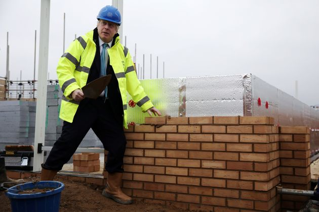 Johnson lays a brick during a Conservative Party general election campaign visit to Barratt Homes's 'Willow...