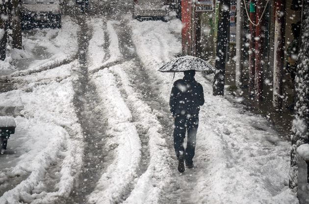 2019/11/09: A resident walks along a snow covered road while holding an umbrella during the heavy snowfall...