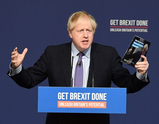 Prime Minister Boris Johnson holds up his party's manifesto during its launch at Telford International...
