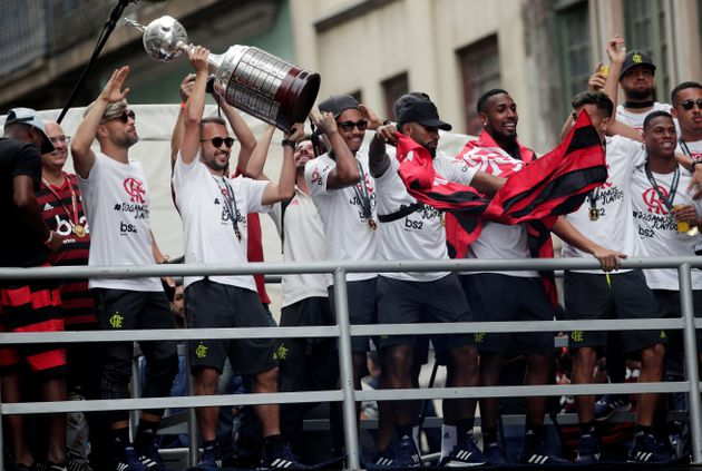 Jogadores do Flamengo exibem a taça da Libertadores da América para sua torcida no centro...