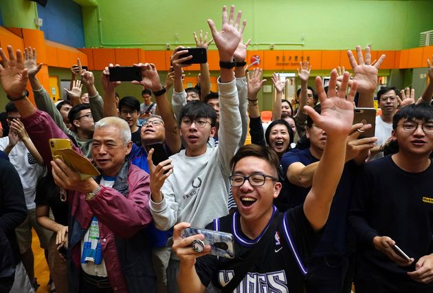 Supporters of pro-democracy candidate Angus Wong celebrate after he won in district council elections...
